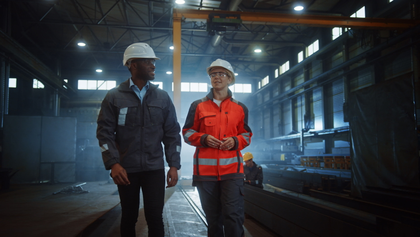 Two Heavy Industry Engineers in Hard Hats Walk in Steel Metal Manufacturing Factory and Have a Discussion. Black African American Industrial Specialist Talk to Female Technician in Manufacture. Royalty-Free Stock Footage #1060203875