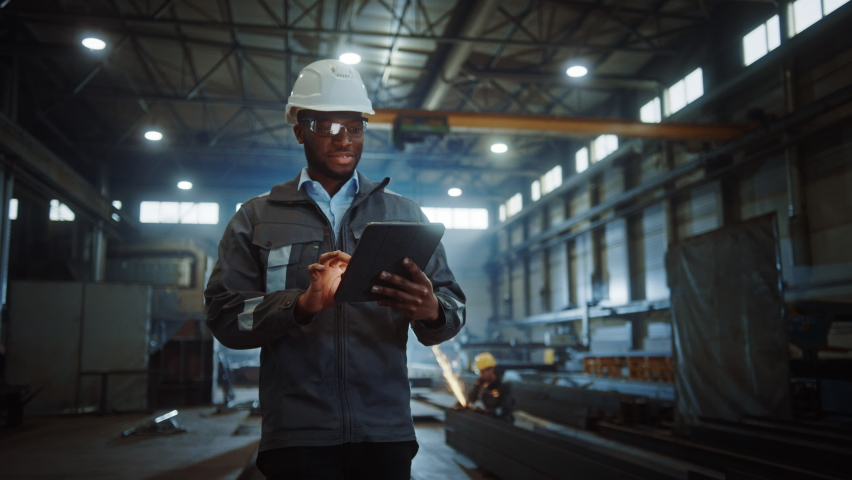 Professional Heavy Industry Engineer/Worker Wearing Safety Uniform and Hard Hat Uses Tablet Computer. Smiling African American Industrial Specialist Walking in a Metal Construction Manufacture. Royalty-Free Stock Footage #1060203890