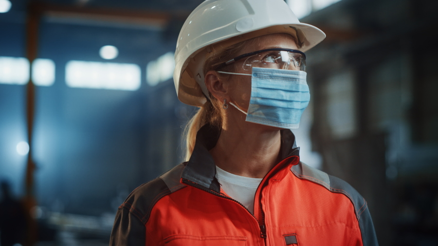 Portrait of a Professional Heavy Industry Engineer/Worker Wearing on Safety Face Mask in a Steel Factory. Beautiful Female Industrial Specialist in Hard Hat Standing in Metal Construction Facility. Royalty-Free Stock Footage #1060203923