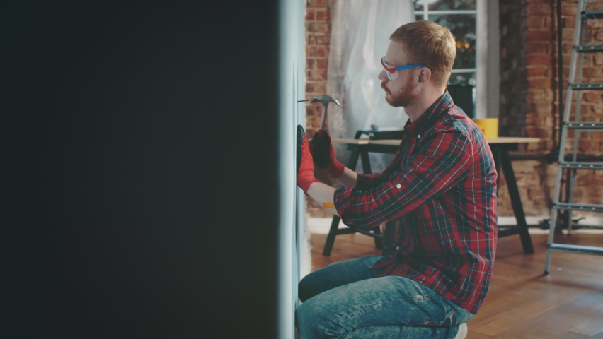 Irritated young man lying on bed cannot rest because of neighbor hammering nail in wall doing house improvement. Noisy neighbor being loud doing renovations | Shutterstock HD Video #1060205048