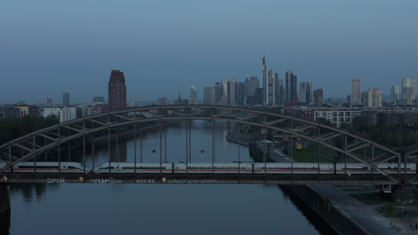 Frankfurt am Main Skyline at Blue Hour early morning over Main River with passanger Train passing bridge, Aerial high angle slow forward