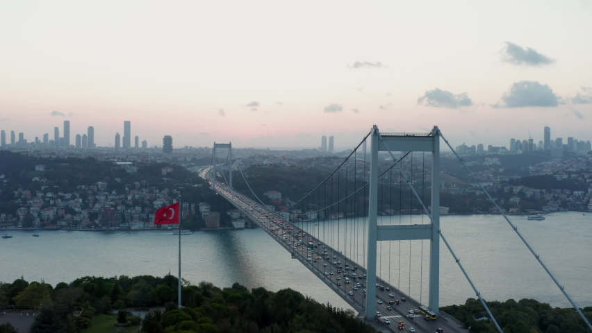 Istanbul 15 July Martyrs Bosphorus Bridge and City Skyline in Background with Turkish Flag at Beautiful Sunset, Aerial slide right | Shutterstock HD Video #1060212494
