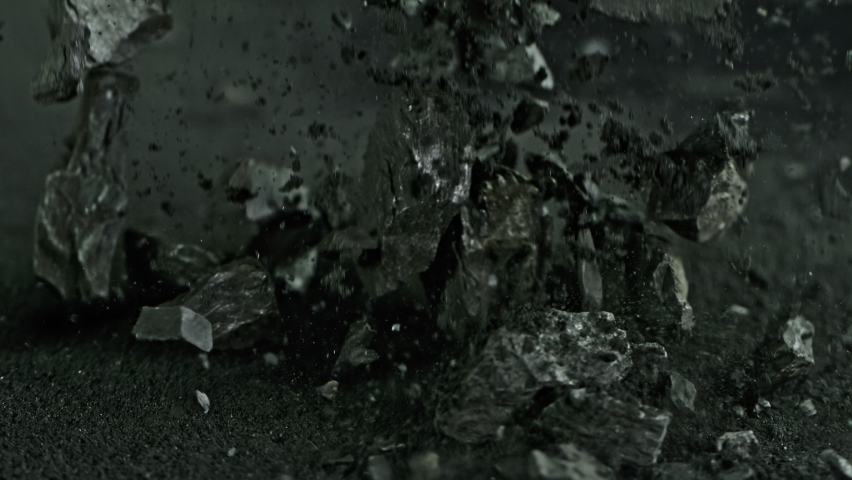 Super Slow Motion Shot of Coal Falling into Black Powder at 1000 fps.