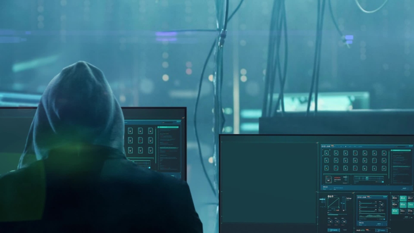 Hacker man sits with his back against the background of working computer screens. Royalty-Free Stock Footage #1060222001