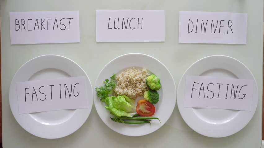 Hands of a woman put a plate with brown rice and vegetables under the title lunch and under the title breakfast and dinner she puts empty plates with titles fasting. Interval fasting concept. Skipping