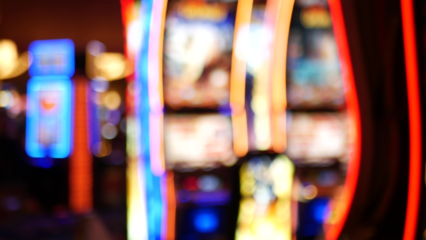 Defocused slot machines glow in casino on fabulous Las Vegas Strip, USA. Blurred gambling jackpot slots in hotel near Fremont street. Illuminated neon fruit machine for risk money playing and betting. | Shutterstock HD Video #1060223915