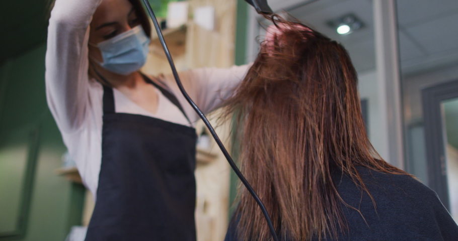 Caucasian female hairdresser working in hair salon wearing face mask, drying hair of female Caucasian customer, slow motion. Health and hygiene in workplace during Coronavirus Covid 19 pandemic.