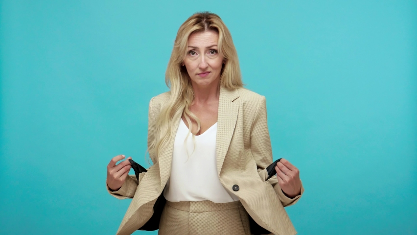 Poor jobless adult woman with blond hair has no money showing empty pockets of her stylish jacket, dismissal, crisis, monetary reform. Indoor studio shot isolated on blue background