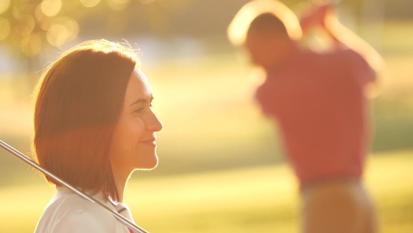 Happy young adult couple playing golf at sunset. Closeup on woman profile, man swinging a golf club and hitting the ball in slow motion, 4K UHD.