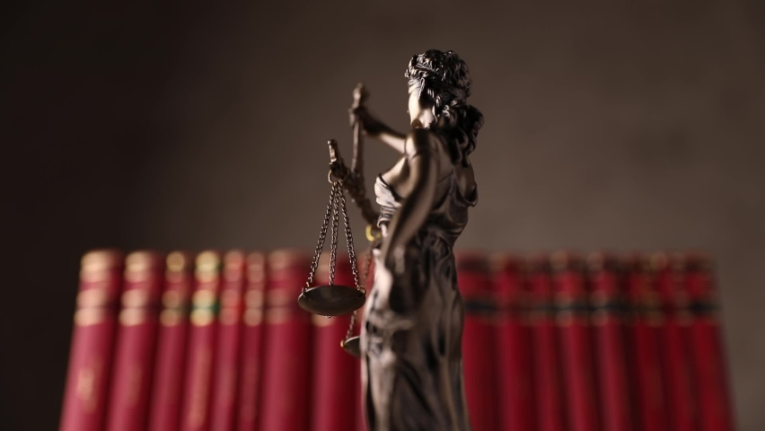 international bronze symbol of law represented by blindfolded goddess holding a balance signifying two broad sources of law, impartiality and power, spinning slowly in front of red books Royalty-Free Stock Footage #1060234055