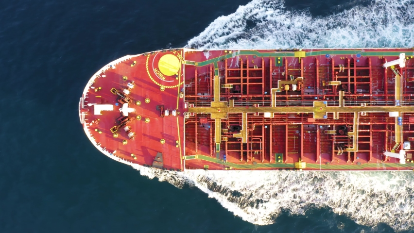 Oil tanker (LPG or chemical) is floating at sea oil port terminal. Oil and gas petrochemical tanker offshore in open sea. Refinery industry cargo ship. Aerial top down view Royalty-Free Stock Footage #1060234091