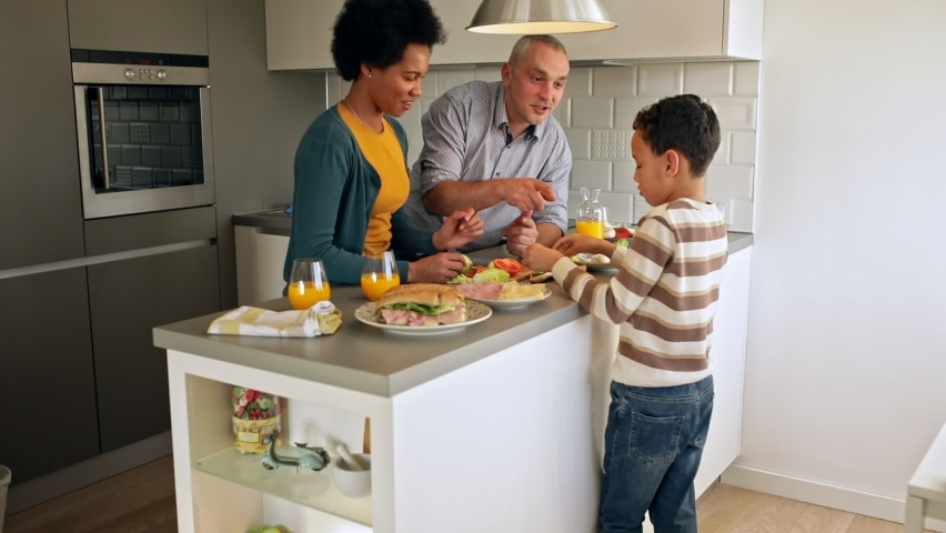 Smiling mixed race family with they son standing in the kitchen preparing sandwich for breakfast at home. | Shutterstock HD Video #1060234187