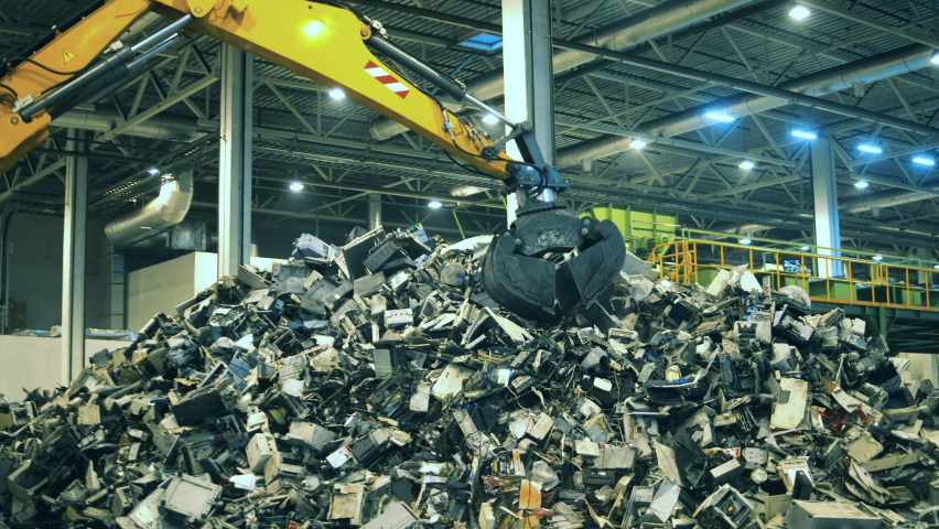 Electronic garbage recycling factory. Fragments of defective electronics being grabbed by a loader Royalty-Free Stock Footage #1060240448