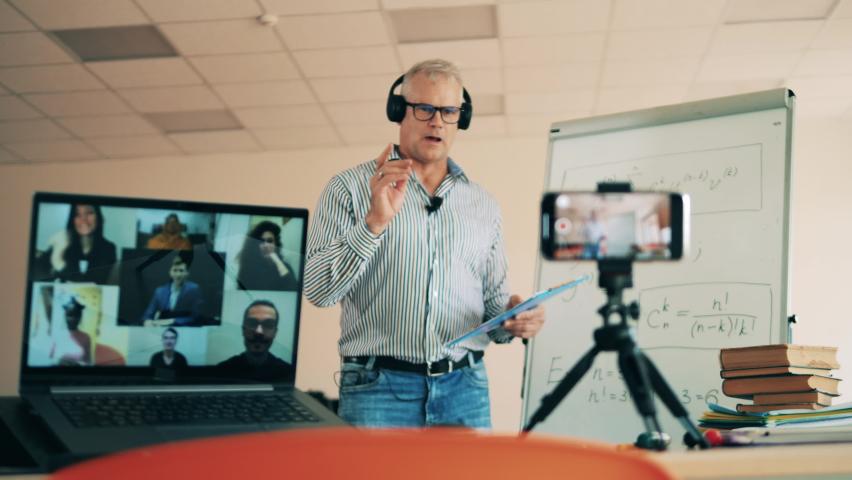 A man is teaching adult students an online class about formulas. | Shutterstock HD Video #1060240535
