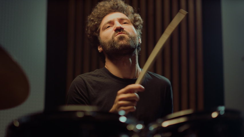 Expressive artist nodding head in concert hall. Emotional drummer hitting drum cymbals in repetition studio. Curly male musician making rock music indoor. | Shutterstock HD Video #1060247840