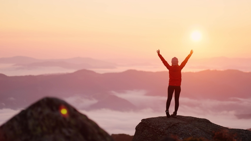 Young woman in orange jacket running up on top of mountain summit at sunset, raises arms into air, happy and drunk on life, youth and happiness. Watching the sunset with beautiful landscape Royalty-Free Stock Footage #1060258418