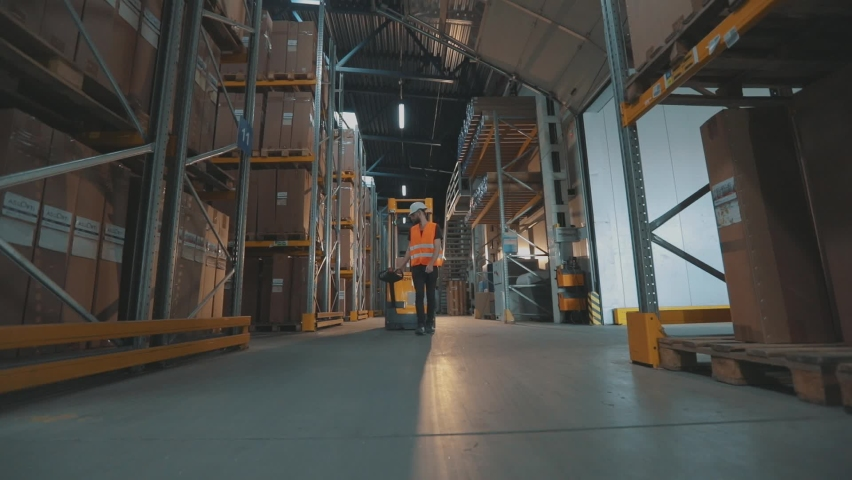 A worker transports cargo through the warehouse. A worker walks through the warehouse with an electric hydraulic forklift. | Shutterstock HD Video #1060260503