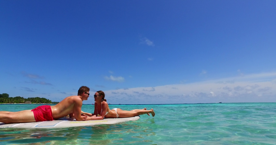Happy couple kissing over surf board floating on crystal emerald water of shallow turquoise lagoon near tropical island on a bright sky background