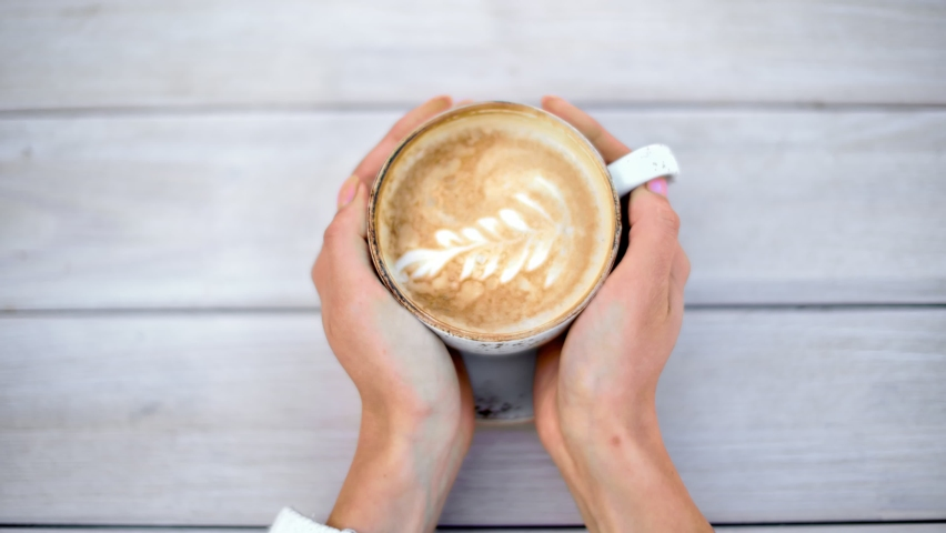 Female hands taking cup of hot cappuccino with latte art from wooden rustic table top view. Woman arms warming holding coffee beverage with white dairy foam. Close up shot on 4k RED camera   Shutterstock HD Video #1060269548