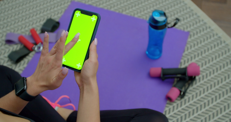 Lviv, Ukraine - October 5, 2020: Fitness woman use smartphone with green screen after training at home. Healthy lifestyle. stretching, leaning forward. Training on distance.
