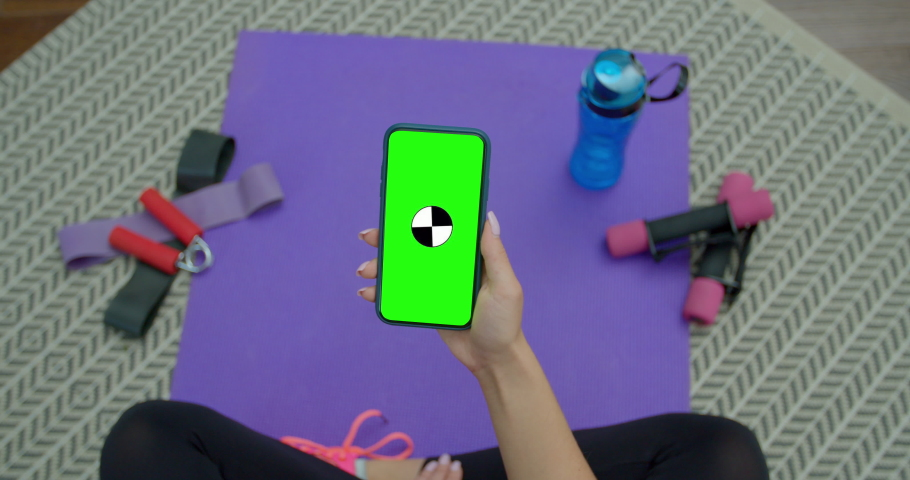 Fitness woman use smartphone with green screen after training at home. Healthy lifestyle. stretching, leaning forward. Training on distance.
