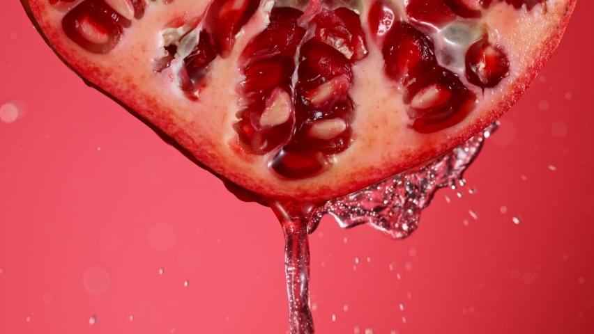 Super Slow Motion of Water Splash on Fresh Backlit Pomegranate Slice. Shot at 1000 fps.   Shutterstock HD Video #1060272794