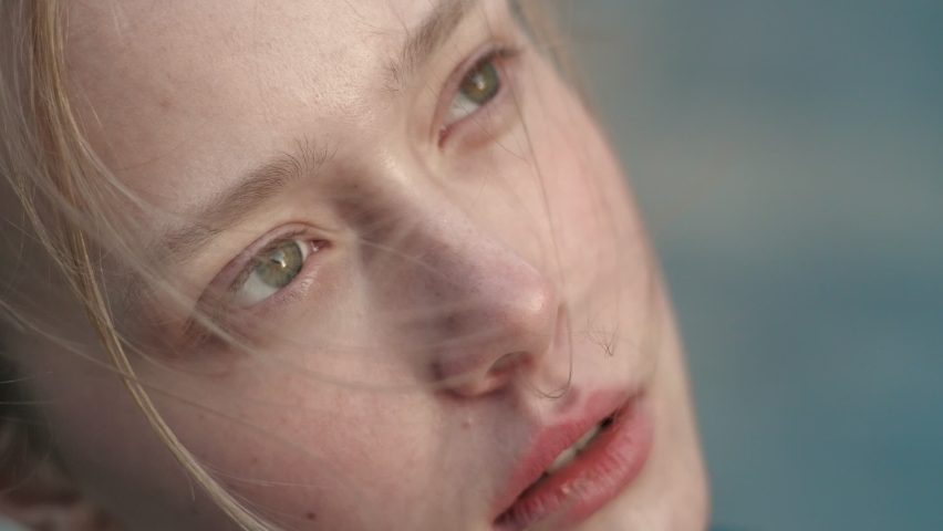 Close up of Woman's Face, Girl opening her Beautiful green Eyes, Wing is blowing her Blonde Hair. Natural Beauty Baby Face Female. Gorgeous woman looking thoughtfully to the Sky. Slow-motion. Royalty-Free Stock Footage #1060273601