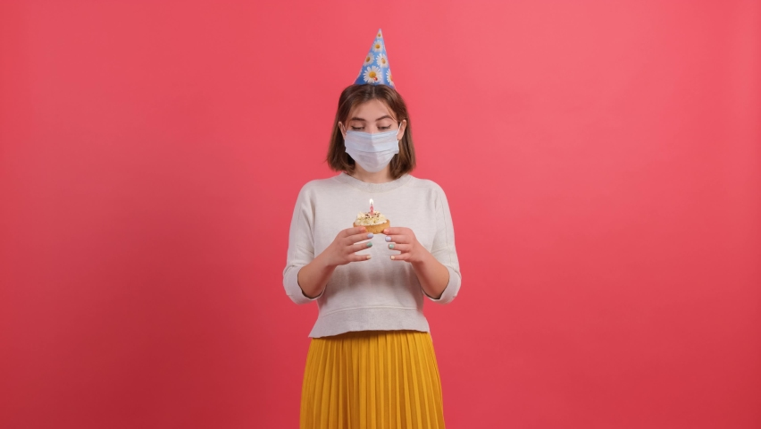 Sad young girl with medical mask on her face and with a birthday hat tries to blow the candle off the cake. Birthday during a pandemic situation. | Shutterstock HD Video #1060286006