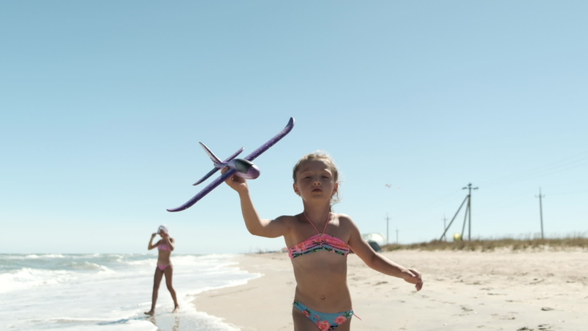 little girl playing on the beach with airplane. Happy girl runs with a toy airplane and drop airplaine. slow motion