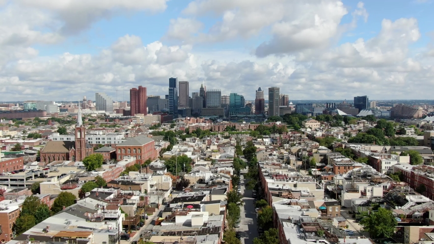 Aerial truck shot, Baltimore Maryland USA skyline, cityscape on summer day, downtown financial business district, neighborhood homes and community housing in foreground