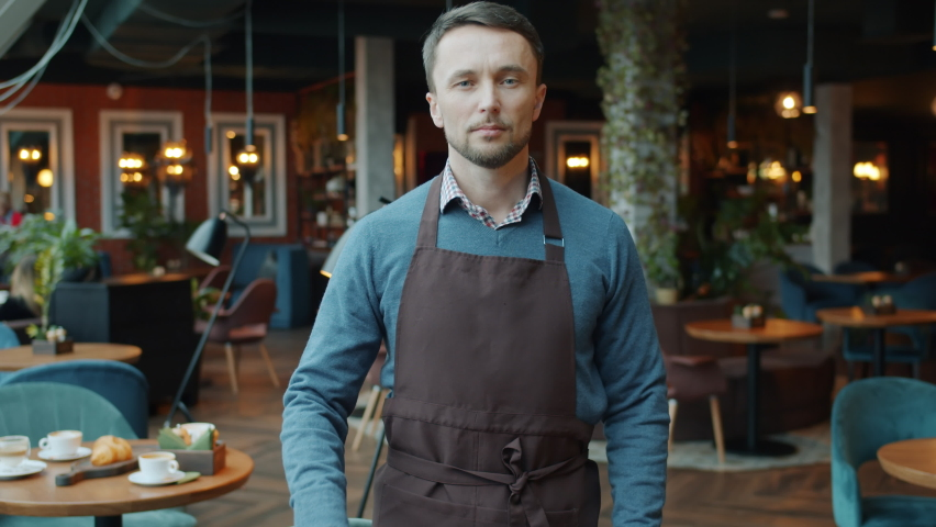 Slow motion portrait of confident young man in apron business owner holding open sign in cafe smiling and looking at camera. People and start-up concept.