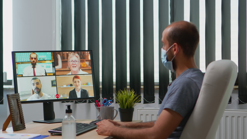 Business man with protective face mask talking on video call on pc while working in new normal office during coronavirus pandemic. Freelancer having online conference meeting using internet technology Royalty-Free Stock Footage #1060310039