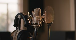 Recording concept. Tracking shot of professional microphone and headphones at sound record studio, close up