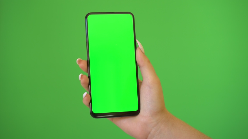 Woman hand holds a smartphone with greeen screen over a green background. | Shutterstock HD Video #1060313897