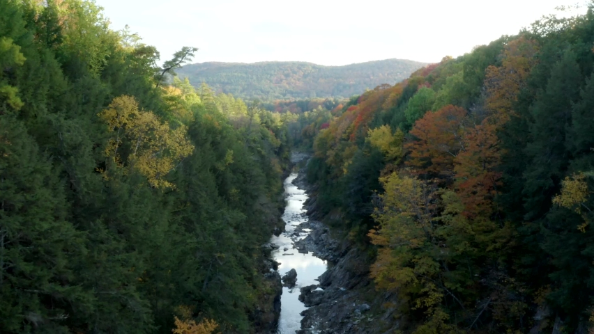 Aerial Drone Flight Through Fall Foliage Inside Quechee Gorge in Vermont, USA Featuring Colorful Autumn Leaves on Trees Along a Creek | Shutterstock HD Video #1060315496