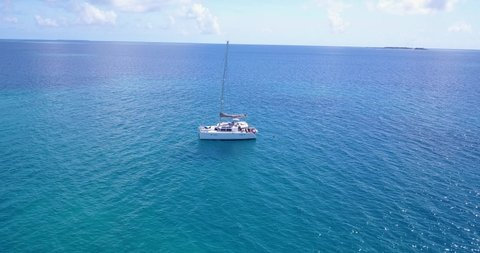 White catamaran anchoring on blue azure calm waters next to tropical island with resorts and villas inside lush vegetation in Caribbean