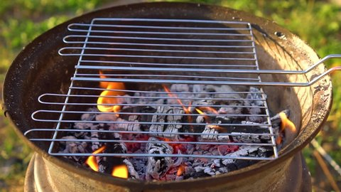 A homemade barbecue with coals burning, a grid for cooking meat is heated on top.