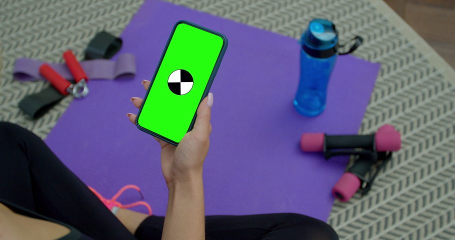 Tired fitness woman use smartphone with green screen after training at home. Workout, training, wellness, sport concept.
