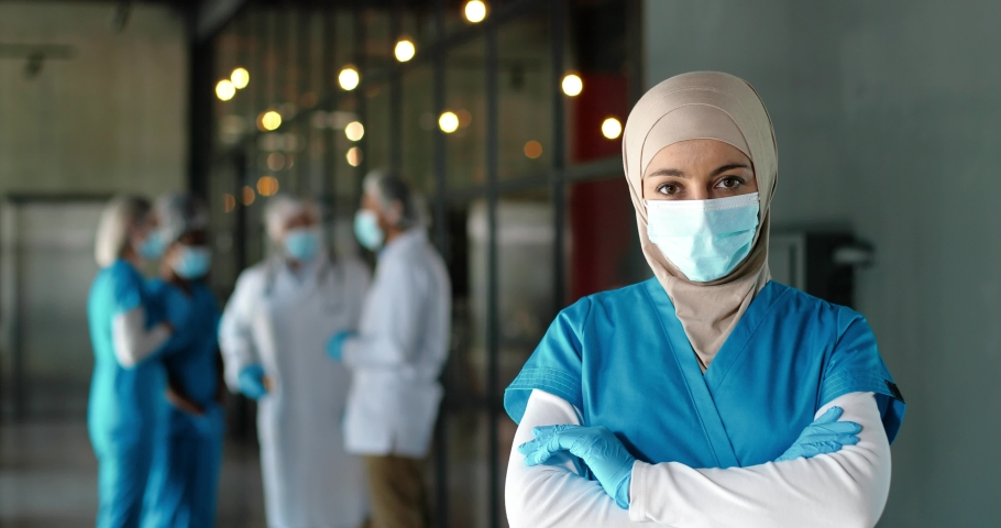 Portrait of Arab woman doctor in hijab, medical mask and gloves standing in hospital. Muslim female medic in traditional headscarf in clinic. Covid-19. Arabian nurse. Coronavirus. Protected. Royalty-Free Stock Footage #1060332050