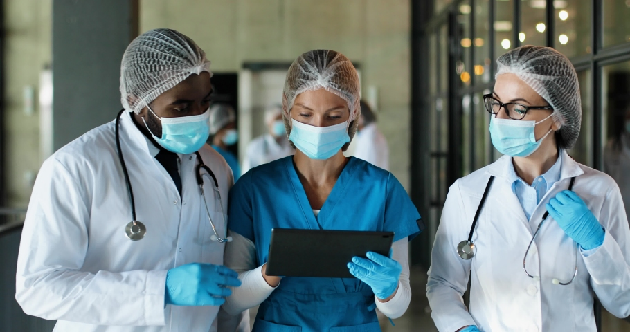 Mixed-races male and females doctors in hats, medical masks and gloves walking in hospital and talking, using tablet device. Multi ethnic man and women, medics discussing diagnosis. Corona concept. Royalty-Free Stock Footage #1060332059