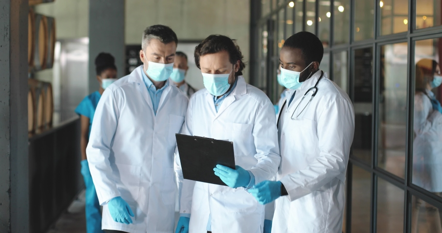 Head of clinic having consultation with doctors. Mixed-races males docs walking in hospital, having conversation and looking at diagnosis. Medics discussing covid-19. Multi ethnic men physicians. Royalty-Free Stock Footage #1060332137