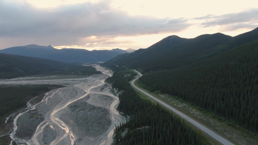 Beautiful View of Scenic Road by Glacial River at Sunset. Aerial Drone Shot. Northern Rocky Mountains, British Columbia, Canada.