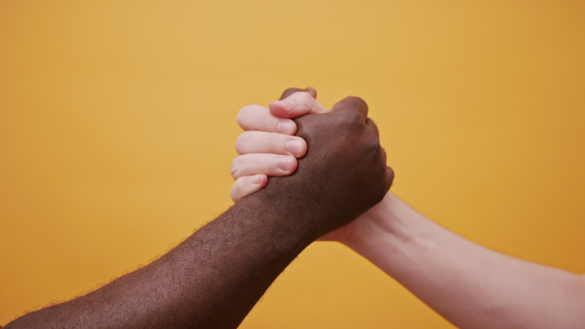 black and white hands holding together, high five shake isolated on the orange background. Close up. High quality 4k footage Royalty-Free Stock Footage #1060345436