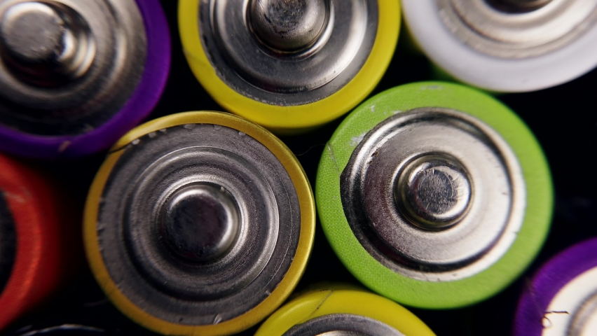 lots of alkaline used AAA batteries background. the video rotation