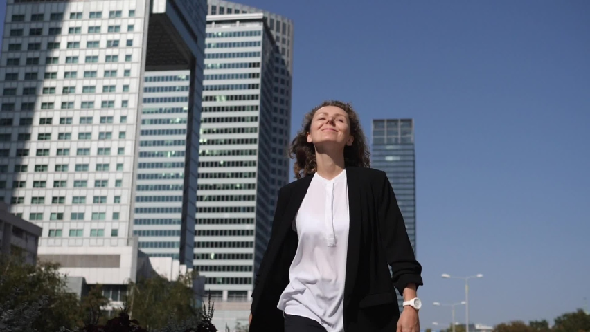 Excited lady in formal office clothes jumping celebrating getting promoted in front of skyscrapers