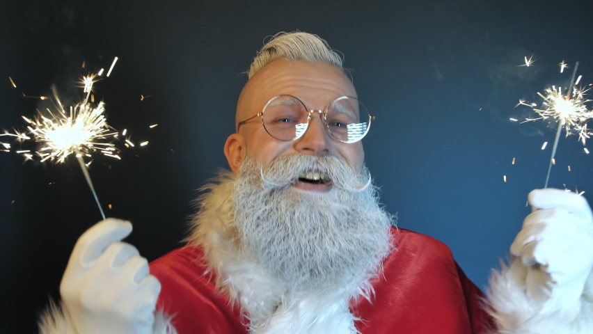 Happy Funny Emotional Santa Claus Sings Song Enjoying Music, Dances Playing with Magical Sparklers, Looking at Camera Closeup Indoors. Positive Festive Mood at New Year, Christmas Holidays Celebration