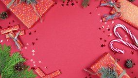 Christmas background 360 degree rotation. Fir tree branches, gift box and confetti star spinning on red background. Concept of New Year presents, festive and holiday shopping