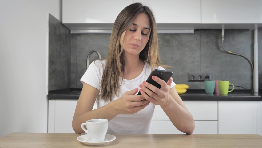 Relaxed young woman using smart phone surfing social media, checking news, or texting messages sitting at kitchen. Millennial lady spending time at home with cell gadget technology. Royalty-Free Stock Footage #1060355729