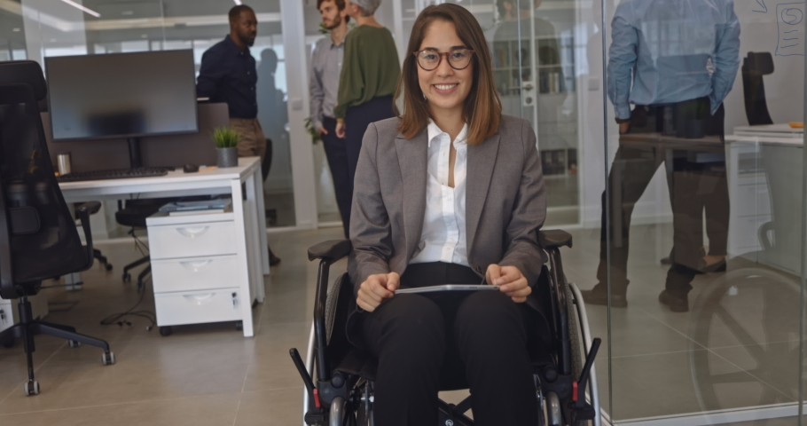 Disabled business woman in wheelchair holding table smiling in office Royalty-Free Stock Footage #1060360142