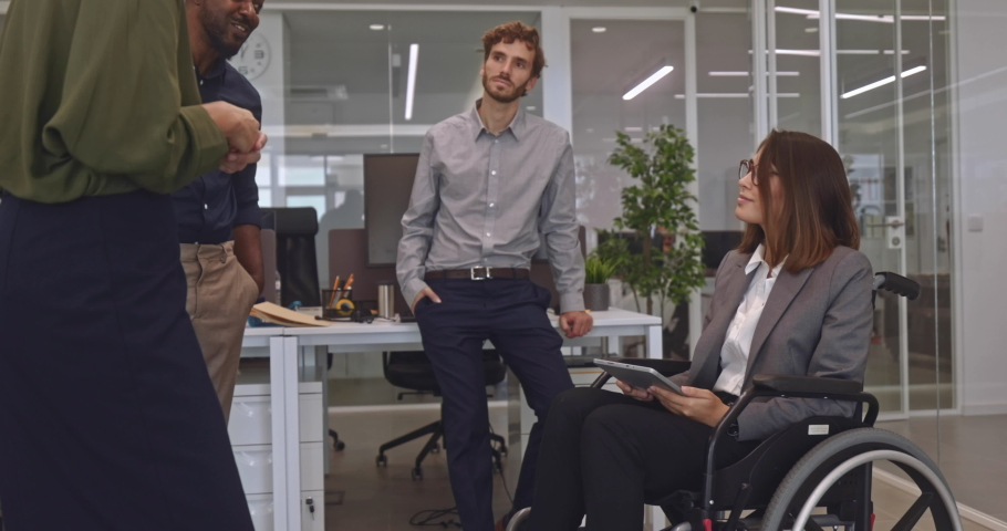 Disabled business woman in wheelchair chatting with coworkers in office Royalty-Free Stock Footage #1060360145